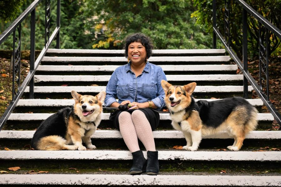 Photo of Luann wearing a chambray top and black skirt, sitting in the middle of two tri-colored corgis.